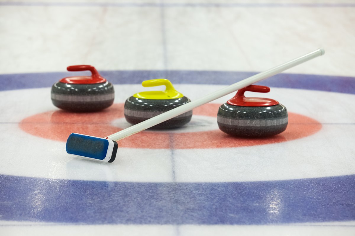 Image of a curling stones and brooms on ice