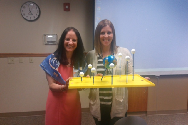 Image of Dr. Carol O'Donnell and Kate Van Eaton holding a Sun, earth, moon board.