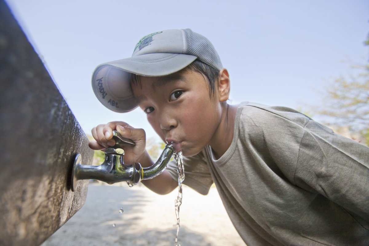 Kid drinking from water faucet