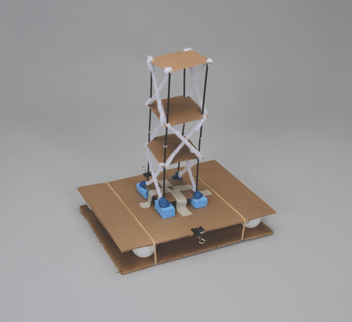 A model of an earthquake-resistant building made out of cardboard, pipe cleaners, and other classroom materials