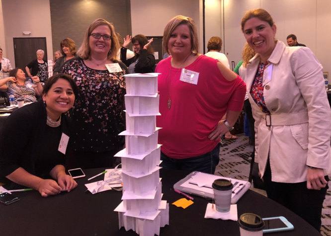 Image of teachers with an index card tower that they created.