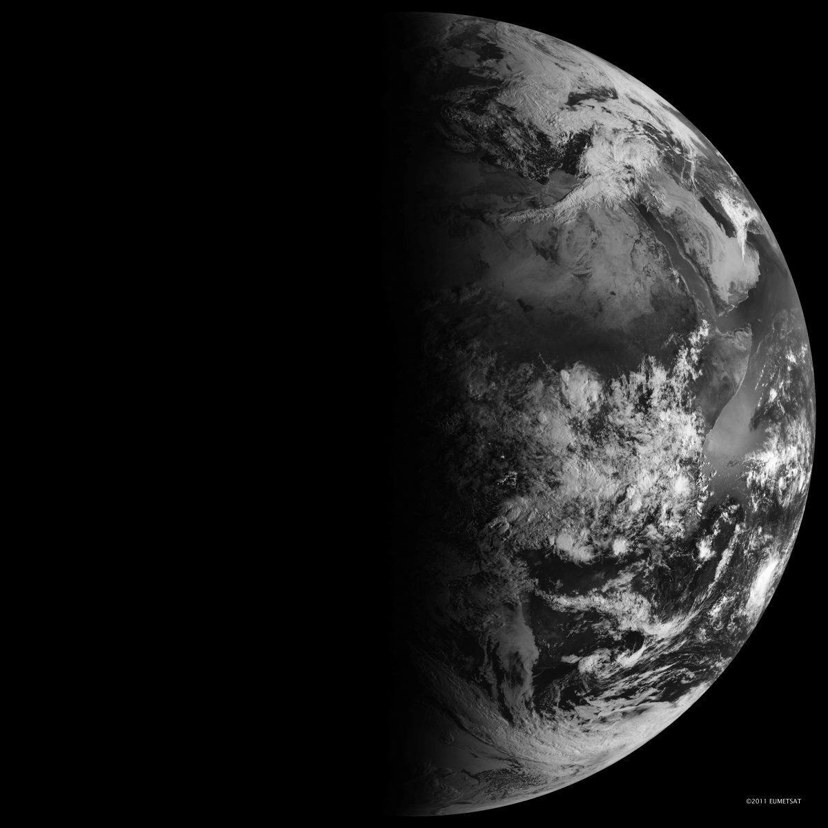 Black and white image of Earth with half illuminated by sunlight and half in darkness