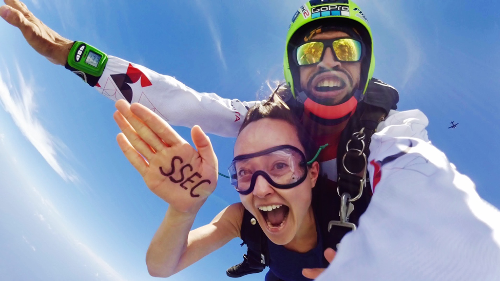 Skydiver in free-fall, hand outstretched. SSEC is written on her hand. Male instructor behind.