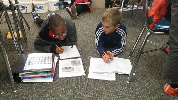 Two students sit on the floor of their classroom and write down information in notebooks.