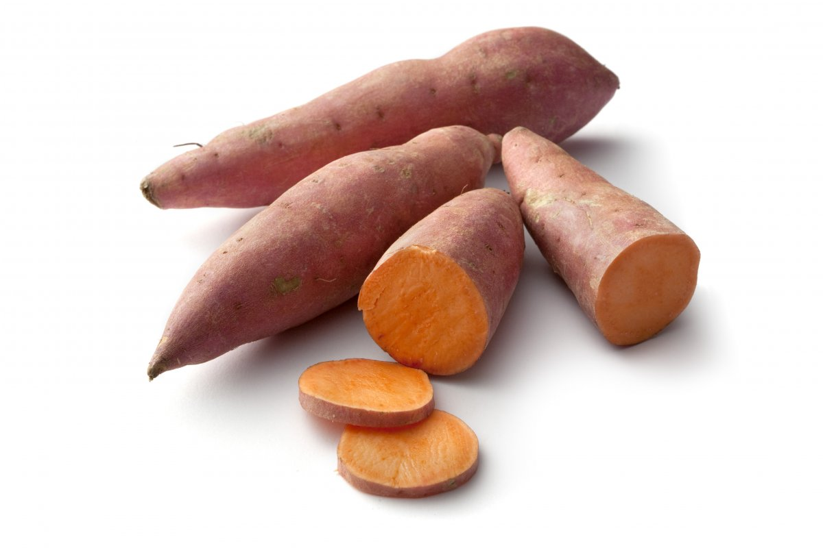 Three sweet potatoes against a white background. Two sweet potatoes are whole and one is cut down the middle with two circular slices cut from it.