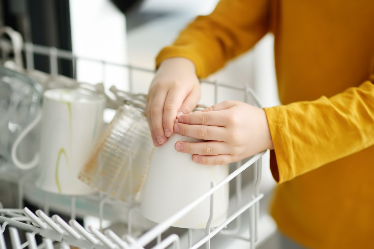 Boy's hands loading a dishwasher