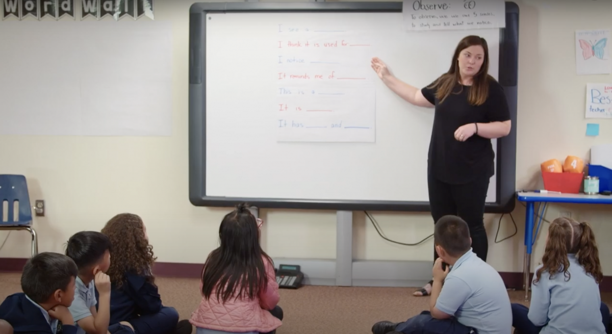 Image of teacher pointing to white board