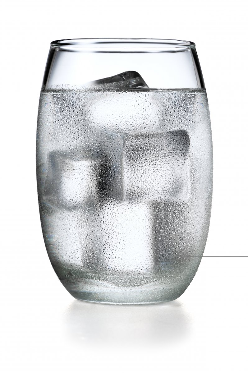 A glass of ice water with condensation