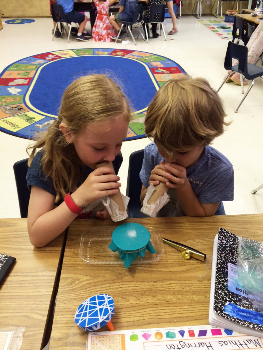 Two students playing kazoos and watching the effect on salt sitting on top of a stretched rubber sheet.