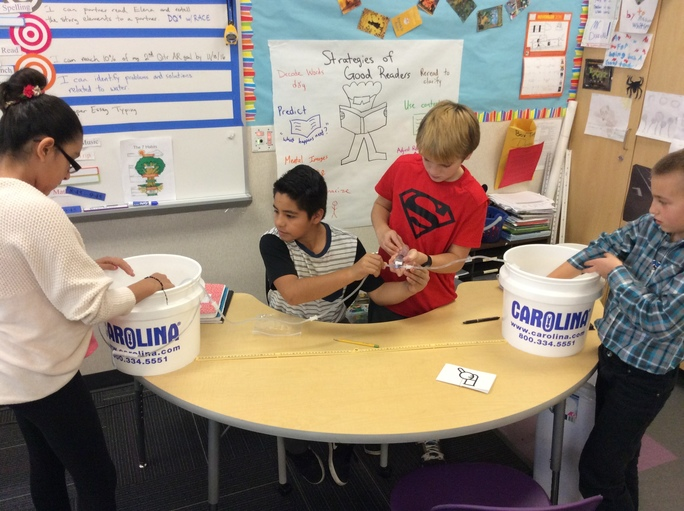 Three students wearing goggles and gloves prepare to filter contaminated water.