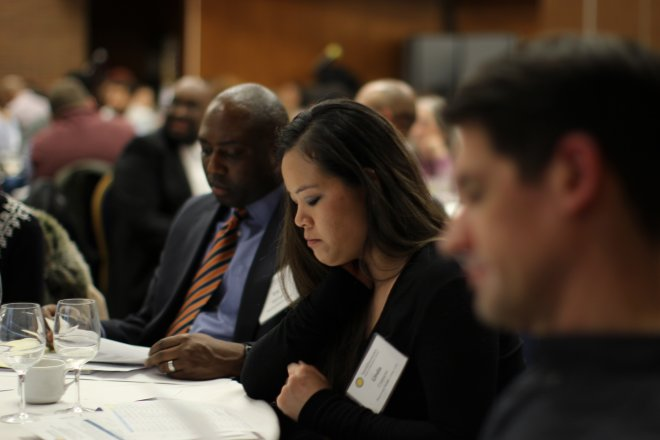 A workshop participant is deep in thought at a table with her peers.