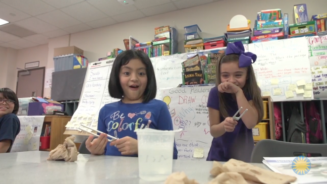 Image of students interacting with a tuning fork during a science experiment